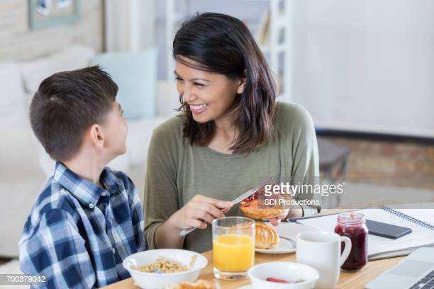 beautiful mid adult asian mom has breakfast with young son - filipino family eating stock pictures, royalty-free photos & images