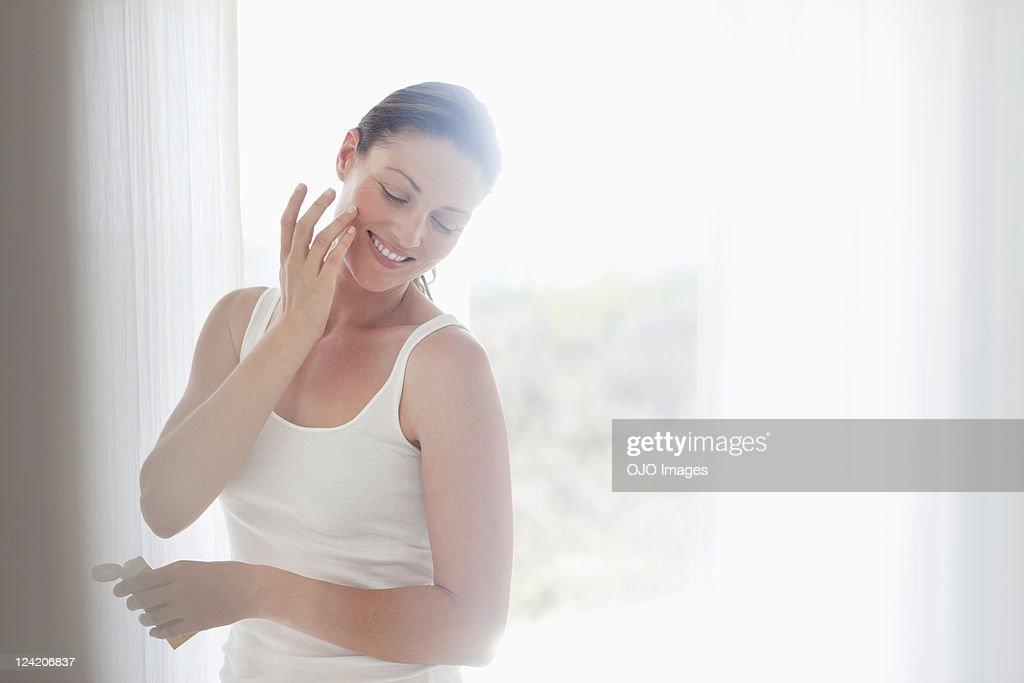 Beautiful mid adult woman applying cream on cheek : Stock Photo