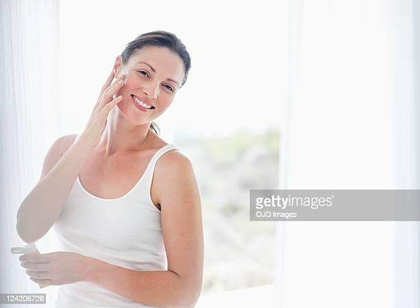 Schöne Mitte Erwachsene Frau Anwendung der Creme auf Wange