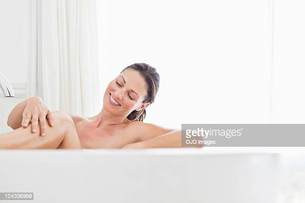 Beautiful mid adult woman smiling in bathtub