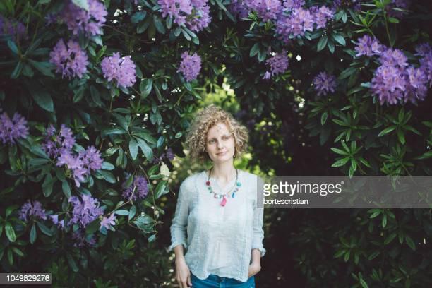 Beautiful Mid Adult Woman Standing Against Purple Flowering Plants