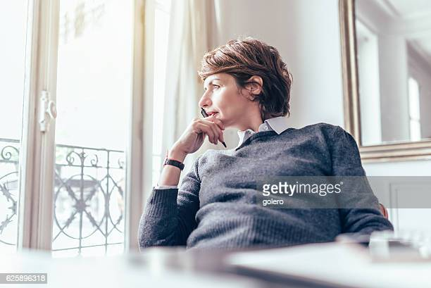 beautiful mid aged french business woman looking out of window - frauen über 30 stock-fotos und bilder