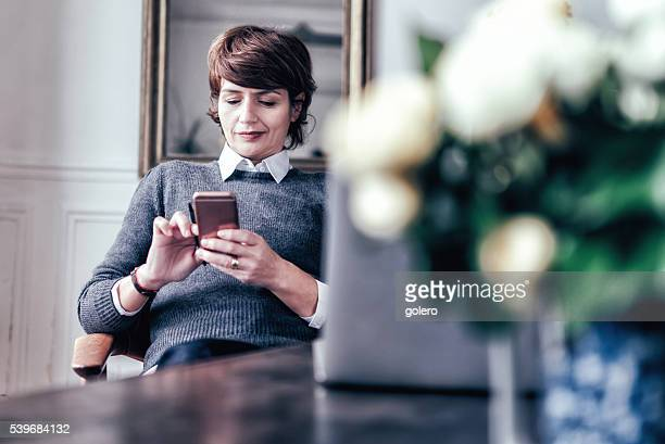 beautiful mid aged french woman with smartphone in Paris apartment