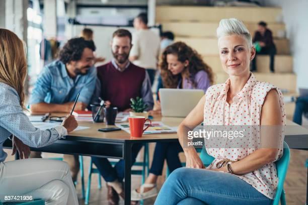 mulher bonita meia-idade com seus colegas no escritório - terceirização - fotografias e filmes do acervo