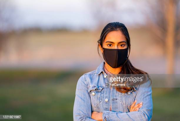 beautiful middle eastern women wearing protective mask outside during sunset - protective face mask stock pictures, royalty-free photos & images