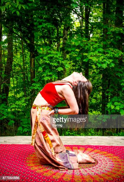 Beautiful, middle-aged woman practising yoga outside in a forest