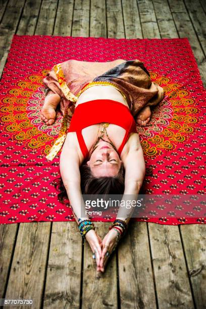 Beautiful, middle-aged woman practising yoga outside on a deck
