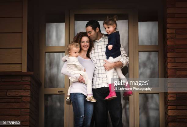 Beautiful Mixed Race Family of Four Poses In Front of Their Home