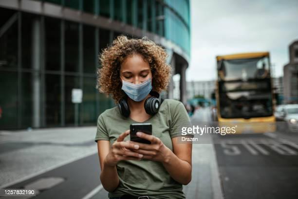 bela garota mestiça sorrindo com máscara facial ao ar livre enquanto espera pelo ônibus - mascara - fotografias e filmes do acervo