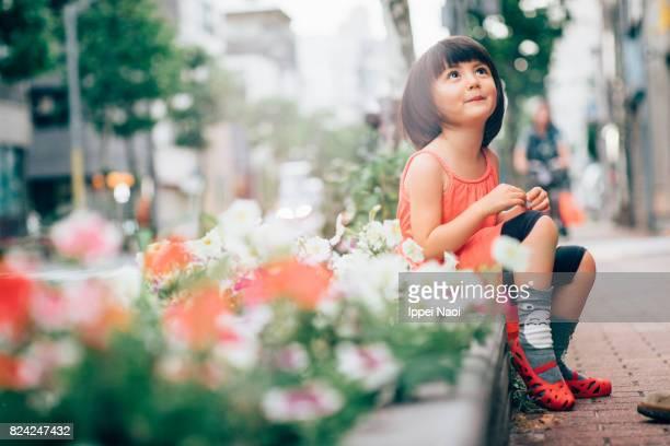 Beautiful mixed race little girl sitting on a pedestrian path