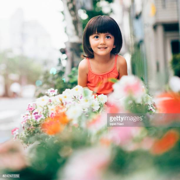 Beautiful mixed race little girl smiling at camera with flowers