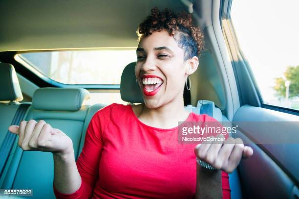 Beautiful mixed race millennial female singing with joy during car pool