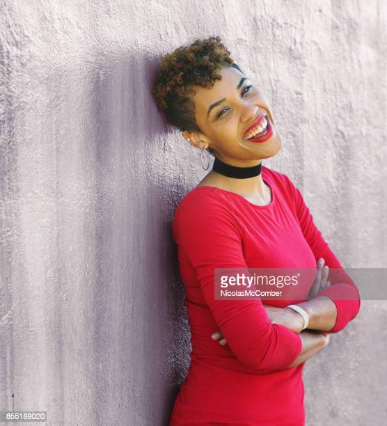 Beautiful mixed race millennial female smiling arms crossed against a wall