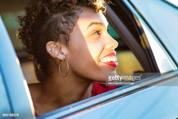 beautiful mixed race millennial female smiling as she looks out car window - hoop earring stock pictures, royalty-free photos & images