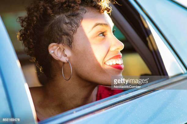 彼女は車の窓の外に見える笑顔美しい混血千年女性 - 輪っかのイヤリング ストックフォトと画像