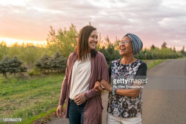 beautiful mixed race mother and daughter relaxing outdoors together - mid adult stock pictures, royalty-free photos & images