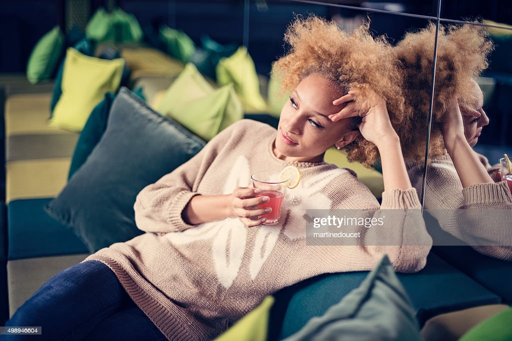 Beautiful mixed race woman having a cocktail on a couch. : Stock Photo