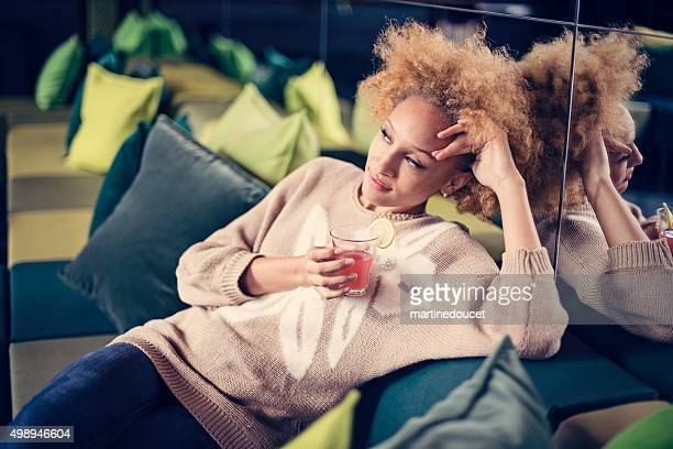 "beautiful mixed race woman having a cocktail on a couch. - ""martine doucet"" or martinedoucet stock pictures, royalty-free photos & images"