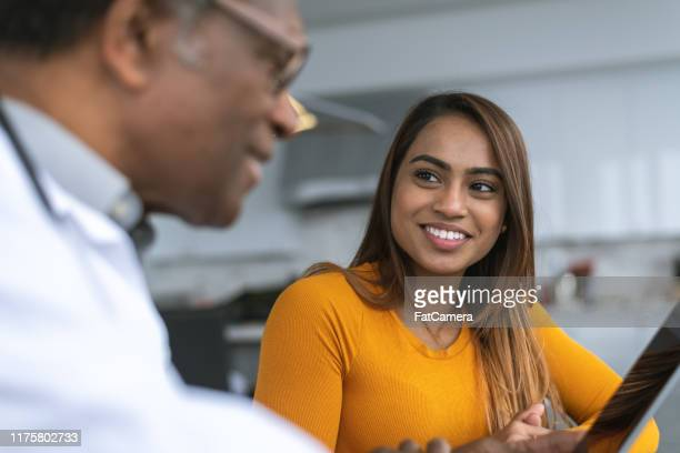 beautiful mixed race woman meets with doctor - women's issues stock pictures, royalty-free photos & images