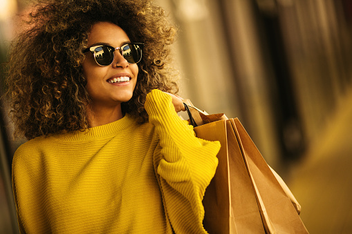 Beautiful mixes race woman holding shopping bags and smiling 1063212632