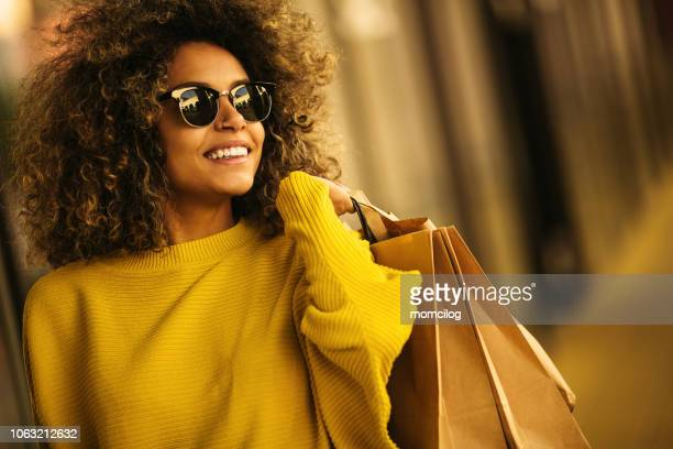 beautiful mixes race woman holding shopping bags and smiling - moda foto e immagini stock