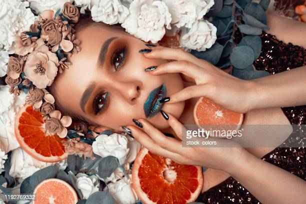 beautiful model posing on a flowerbed - grapefruit red stock pictures, royalty-free photos & images
