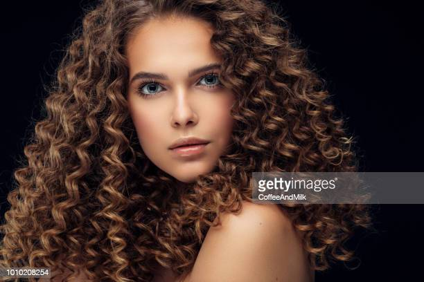 beautiful model with long curly hair - frizzy stock pictures, royalty-free photos & images