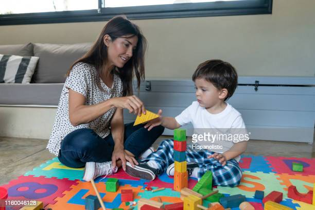 beautiful mom and son playing with wooden building blocks at home - hispanolistic stock photos and pictures