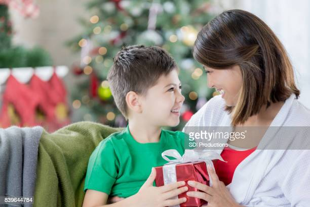 beautiful mom gives christmas present to cute son - filipino christmas family stock pictures, royalty-free photos & images