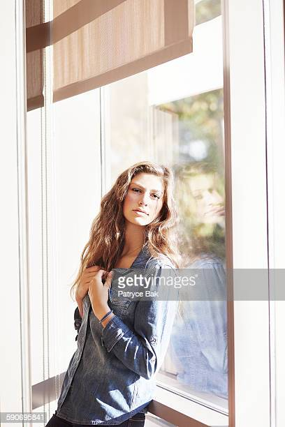 Beautiful, moody woman with reflection in window