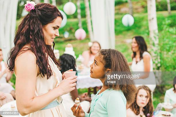Beautiful mother and daughter at a garden party