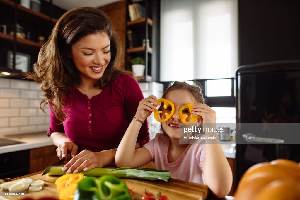 Beautiful mother and daughter in the kitchen : Stock Photo