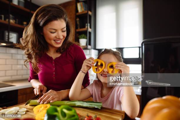 Beautiful mother and daughter in the kitchen