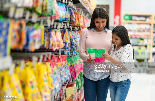 schöne mutter und tochter mit blick auf ein produkt im supermarkt beide lächelnd - kuchen und süßwaren stock-fotos und bilder