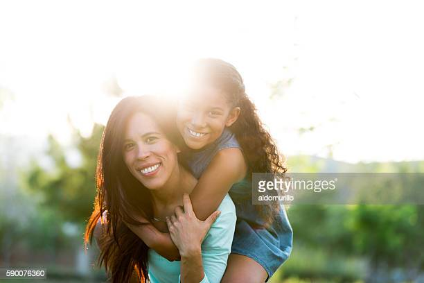 beautiful mother and daughter outdoors in backlight - mexican mom stock photos and pictures