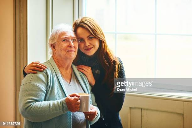 beautiful mother and daughter standing together at home - british granny stock photos and pictures