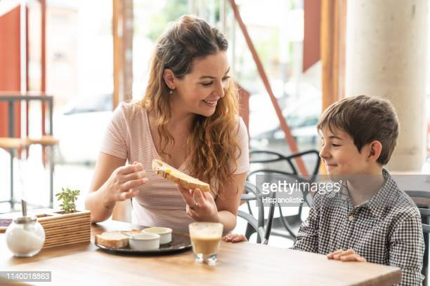 beautiful mother and son talking while she spreads butter on toast both smiling - hispanolistic stock photos and pictures
