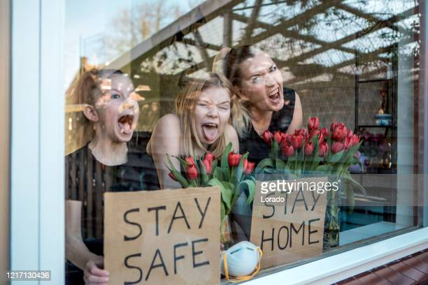 a beautiful mother and two young daughters at home during the lockdown - illness prevention stock pictures, royalty-free photos & images