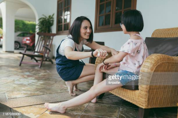 beautiful mother apply medicine on daughter hand - ibnjaafar stock photos and pictures
