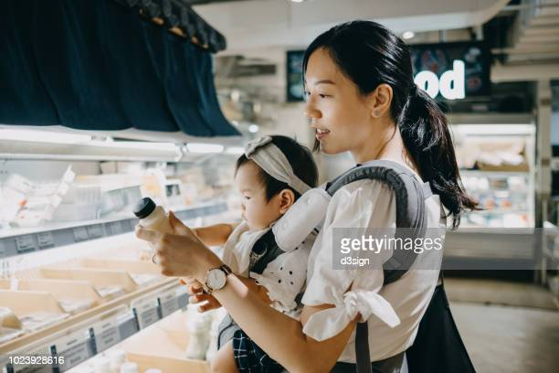 Beautiful mother carrying cute baby girl grocery shopping in supermarket and reading nutrition label on a bottle of fresh organic soy milk