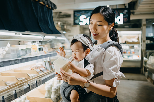 Beautiful mother carrying cute baby girl grocery shopping in supermarket and reading nutrition label on a packet of fresh organic tofu - gettyimageskorea