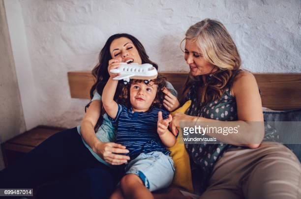 Belle mère, fille et petit-fils jouer des avions à la maison
