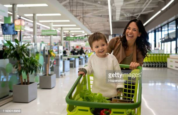 beautiful mother pushing cart with her toddler inside with purchased groceries leaving the supermarket and facing camera smiling - family with one child stock pictures, royalty-free photos & images