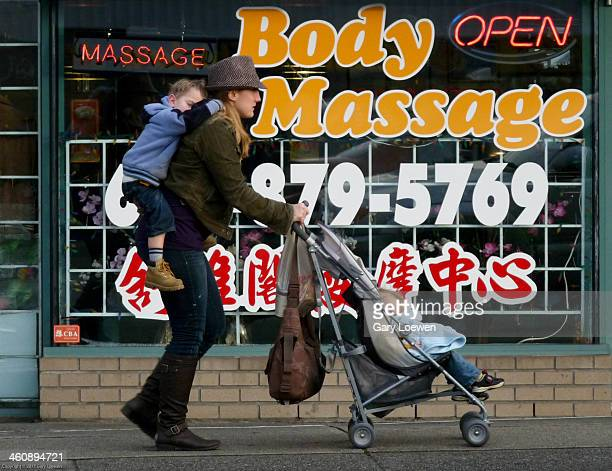 Beautiful mother pushing one child in a stroller while carrying another child on her back outside of a Massage Parlor on Main Street in Vancouver B.C.