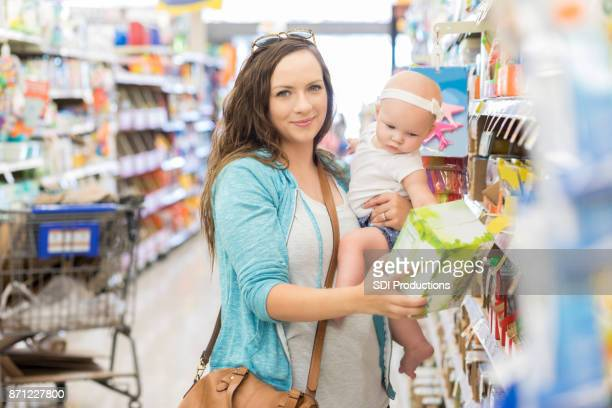 Beautiful mother reads product label while shopping in grocery store