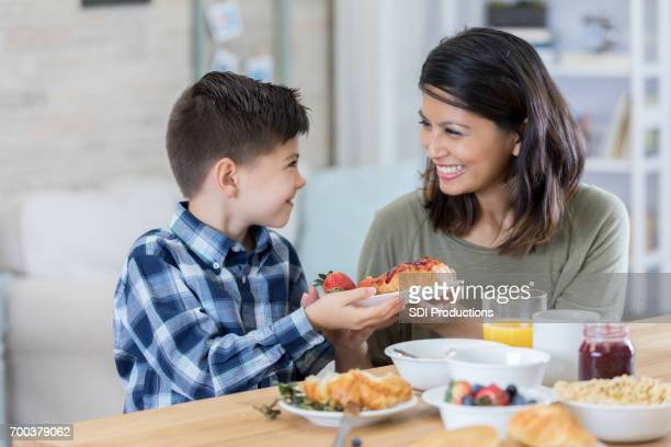 beautiful mother serves her son breakfast - filipino family eating stock pictures, royalty-free photos & images