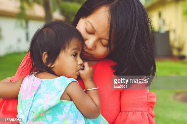beautiful mother snuggles with toddler daughter in an outdoor portrait - vietnamese ethnicity stock pictures, royalty-free photos & images