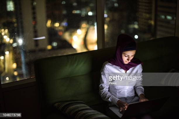 beautiful muslim woman answering e-mails after work - muslim woman darkness stock photos and pictures