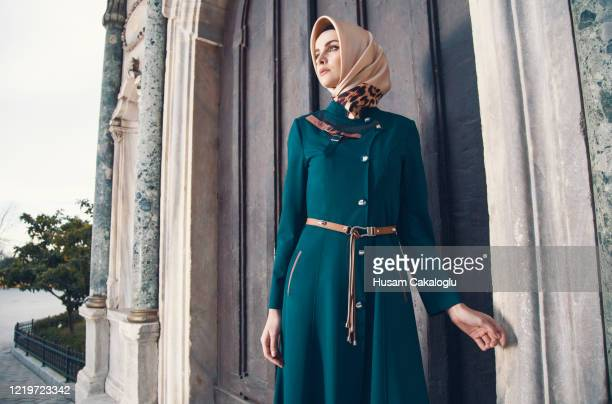 beautiful muslim woman standing in front of caravanserai gate - headwear stock pictures, royalty-free photos & images