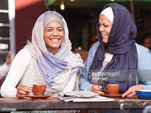 美しいイスラム教徒の女性笑うコーヒーを飲みながらます。